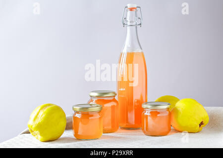 Homemade quince jelly and Juice in a bottle and glass jars with quinces on a linen tablecloth in front of a neutral background, copy space. - Stock Image
