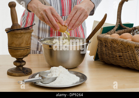 Hands adding egg to a bowl, surrounded by the other ingredients and a recipe book. - Stock Image
