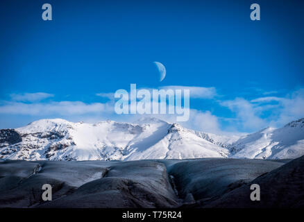 Huge majestic glacier's icy surface by snowy mountain in Iceland - Stock Image