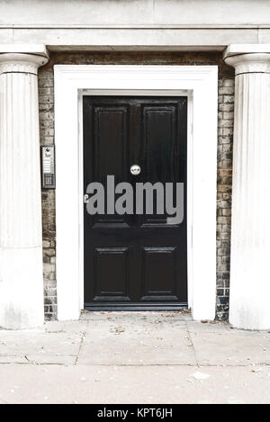 Black vintage wooden door entrance with a silver knocker and white stone columns set in brickwork - Stock Image
