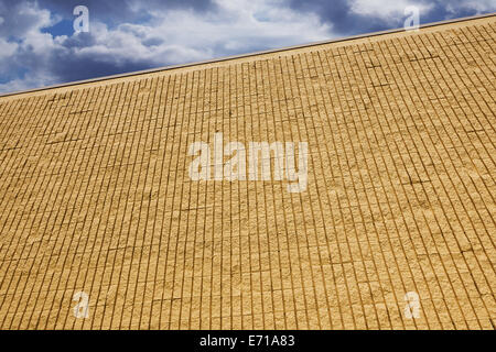 yellow brick wall with clouds - Stock Image