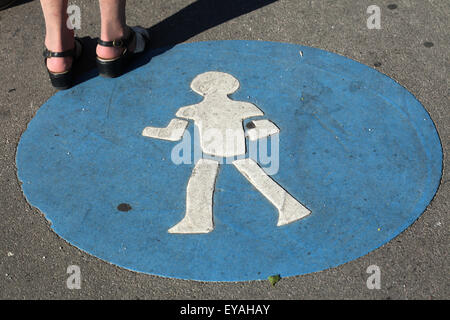 Woman stands next to a blue pedestrian walkway sign in Vienna, Austria. - Stock Image