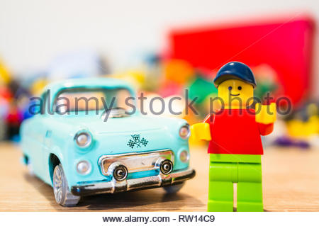 Poznan, Poland - February 15, 2019: Lego man figurine standing next to his parked old time car. Proud owner of his vintage vehicle. - Stock Image