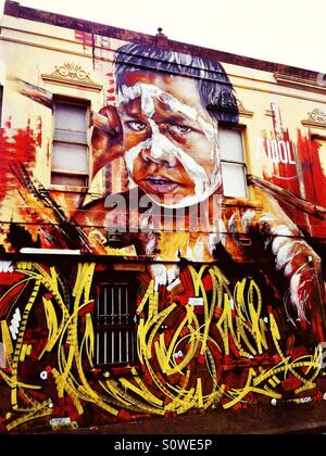 Street art on building of Australian indigenous boy with face paint in Melbourne - Stock Image