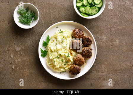 Minced meat cutlets with mashed potatoes on white plate over brown background. Top view, flat lay - Stock Image