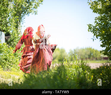 Two young women in traditional russian clothes stand in the field between the trees - holding hadns backview - Stock Image