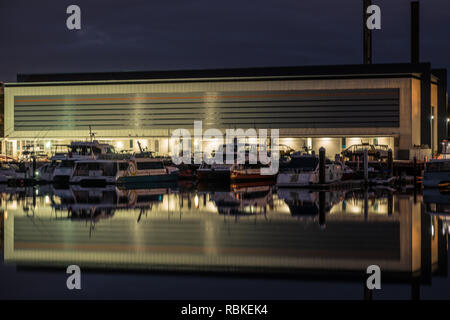 boat storage and boats reflected on calm water - Stock Image