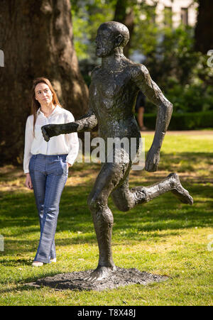 A Christie's employee views 'Running Man (Front Runner) by Dame Elisabeth Frink, valued at £400,000 to £600,000, part of the Christie's Sculpture in the Square exhibition which takes place in St James's Square, London until June 17 2019. - Stock Image