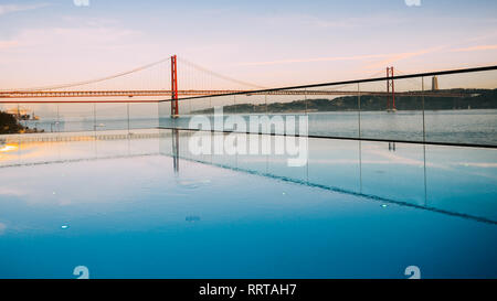 Sunset over the '25 of April' Bridge in Lisbon, Portugal with reflection from infinity pool. - Stock Image