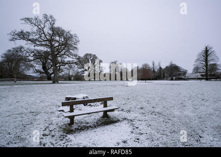 Snowy winter scene with snow covered bench at Inch Field, Cahir, Tipperary, Ireland - Stock Image