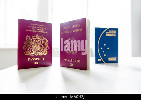 British and Italian passports standing next to each other, with Brazilian passport out of focus and white light exploding in the background. - Stock Image