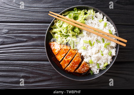 Teriyaki chicken with rice garnish and salad close-up on a plate on the table. horizontal top view from above - Stock Image