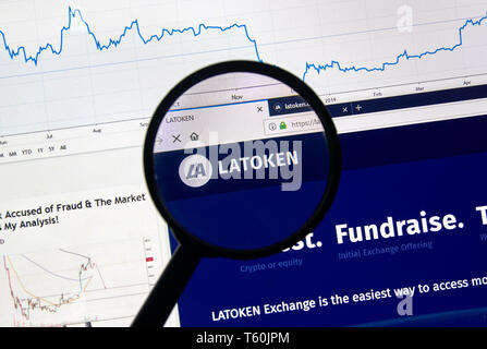 MONTREAL, CANADA - APRIL 26, 2019: Latoken cryptocurrency digital assets exchange logo and home page on a laptop screen under magnifying glass. - Stock Image