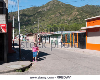 Two women walk by middle class houses in Jinotega, Nicaragua. - Stock Image