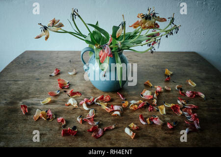 Dead flower petals falling from stems in vase - Stock Image