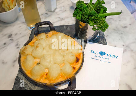 Fish Pie topped with Parmesan Mash and served with greens and a half a pint of lager seaside meal at the Seaview Café Saltburn North Yorkshire UK - Stock Image