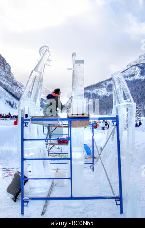 LAKE LOUISE, CANADA - JAN 22, 2011: An ice sculptor carves a tall block of ice with a carving tool during the annual Ice Magic Festival held in the Ca - Stock Image