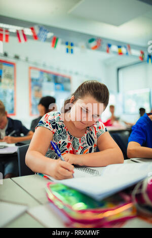 Focused junior high school girl student doing homework at desk in classroom - Stock Image