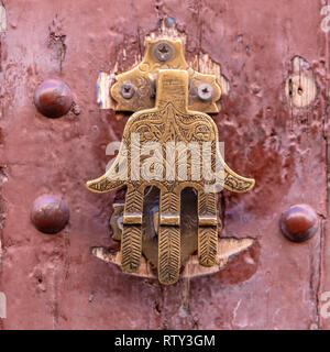 Brass door knocker in shape of jewish hand symbol on door in kasbah, Morocco - Stock Image