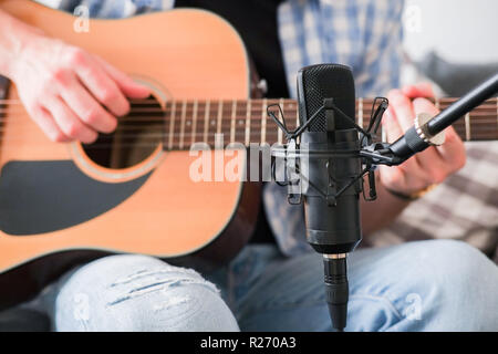 Young male recording his acoustic guitar with condenser microphone - Stock Image