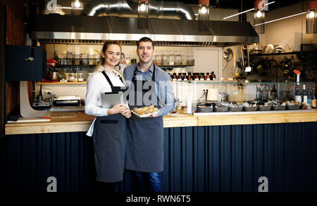 Young entrepreneurs inside their restaurant. Proud of their business. Start-up - Stock Image