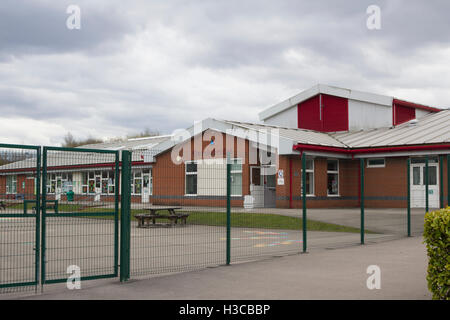 High wire security fencing surrounds the playground at Queensbridge primary school, St. Germain Street, Farnworth. - Stock Image