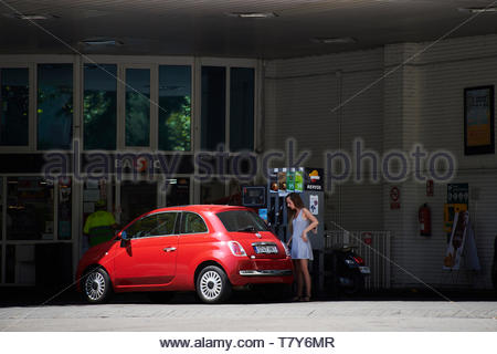 Red car filling up with petrol in garage on  Street in the City of Barcelona in Catalunya in Spain in Europe - Stock Image