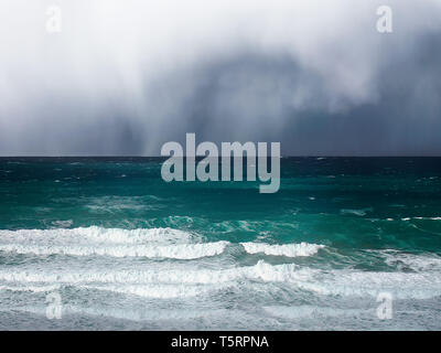 stormy clouds and rain on a sea with waves - Stock Image