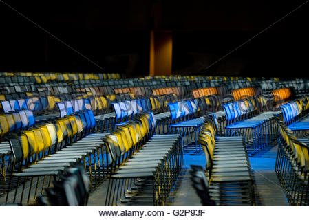 Rows of chairs set up for a business conference in auditorium at night with colored lights side view shallow depth - Stock Image