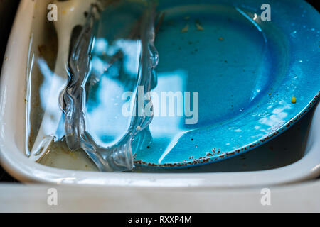Unwashed dirty dishes soaking in a sink. - Stock Image