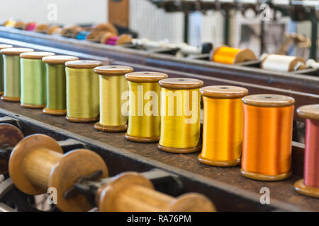Whitchurch Silk Mill in Hampshire, UK - close-up of colourful silk yarn on bobbins ready for spinning - Stock Image