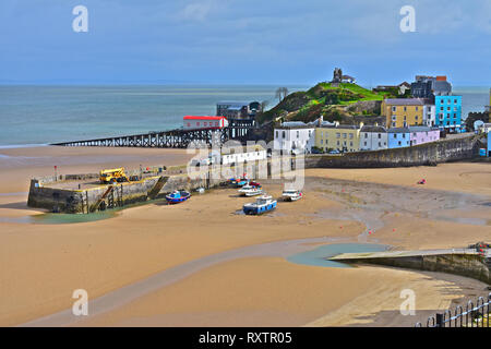 The pretty harbour at Tenby, low tide in Winter. Lifeboat stations old & new  with pastel coloured houses overlooking the sandy North Beach.S.Wales - Stock Image