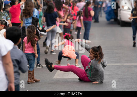 Children scramble to grab candy and beads thrown from floats onto street during annual Washington's Birthday Celebration parade in downtown Laredo TX. - Stock Image