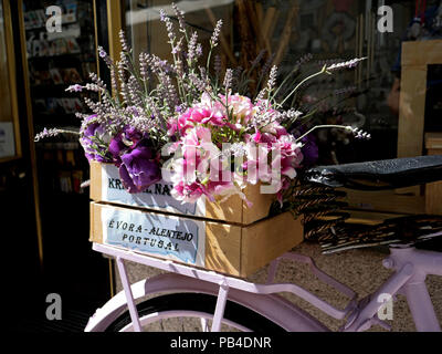 Decorative, bouquet of flowers on a pink bicycle outside a shop in the town centre of the city of Evora, Portugal - Stock Image