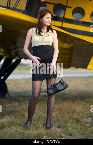Fanciful young woman is standing besides Yellow biplane airplane - Stock Image
