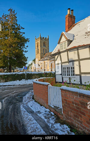 St Peter's church, Welford on Avon, Warwickshire, on a winter morning, with blue sky following a light snowfall. - Stock Image