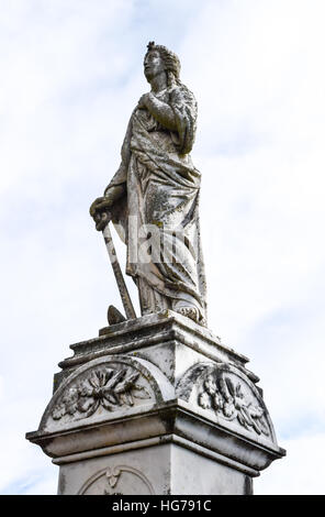 A tall stone sculpture atop a column stands watch over the grave below. - Stock Image