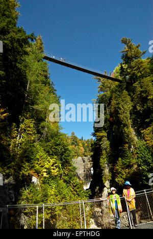 Visitors crossing Park Canyon Ste Anne River pedestrian suspension bridges - Stock Image