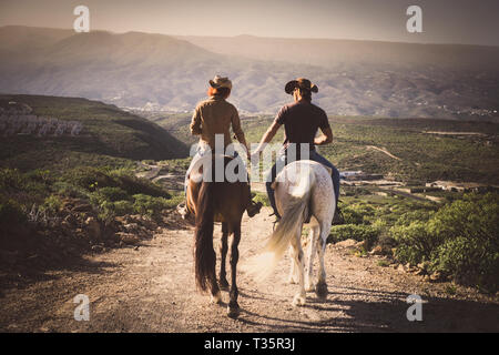 Romantic couple wide horses together holding hands with love and romance in outdoor leisure lifestyle alternative activity - viewed from back young pe - Stock Image