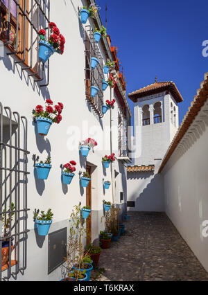 The minaret of the Mezquita Grande Mosque, viewed from a florally decorated alley in the El Albayzín or Albaicín quarter of Granada, Andalucia, Spain - Stock Image