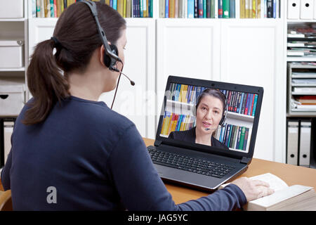 Woman with headset and book at her desk in front of her laptop having an online chat with her lawyer, text space - Stock Image