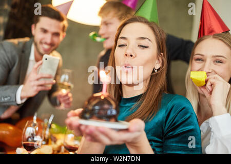 Woman blows out cake on birthday party and is photographed for Foodblog - Stock Image