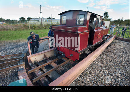 The driver and fireman use the Turntable at Wroxham station terminus to turn their 15-Inch narrow gauge steam locomotive - Stock Image