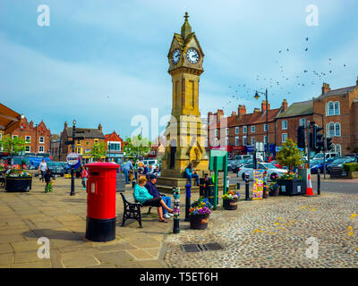 The town clock and a bright red Post Box in the Market Place with people enjoying spring sunshine in Thirsk North Yorkshire UK - Stock Image