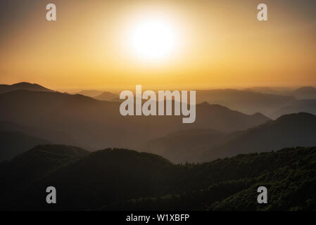Beautiful clear sky summer sunset in the mountains. Landscape with sun light shining - Stock Image