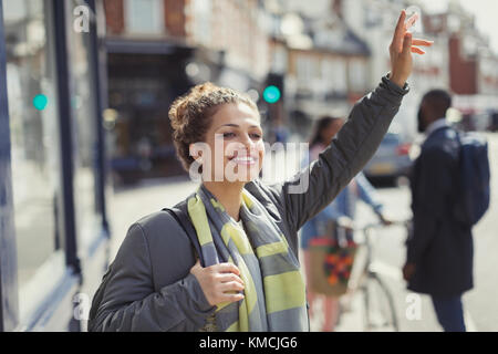 Smiling young woman hailing taxi on sunny urban street - Stock Image