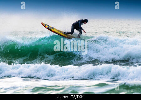 A surfer riding a longboard on the crest of a wave at Fistral in Newquay in Cornwall. - Stock Image