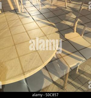 Wooden table and chair seen through glass wall reflecting outdoor tile floor. - Stock Image