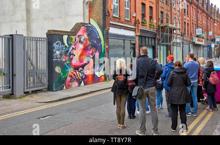 LONDON ENGLAND BRICK LANE GROUP OF PEOPLE STUDYING WALL ART IN THE AREA - Stock Image