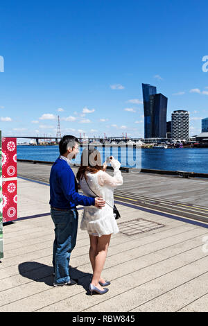 Male and female Chinese students touring in Melbourne Docklands,Victoria Australia. - Stock Image